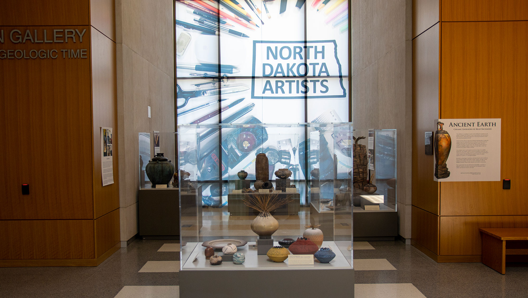 Hallway with display cases containing pottery. In the background is a window with a window cling that reads North Dakota Artists and has art supplies around the text