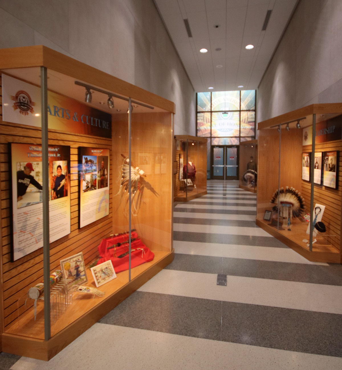 Hallway with exhibit cases with images of Native Americans and artifacts relating to those pictured