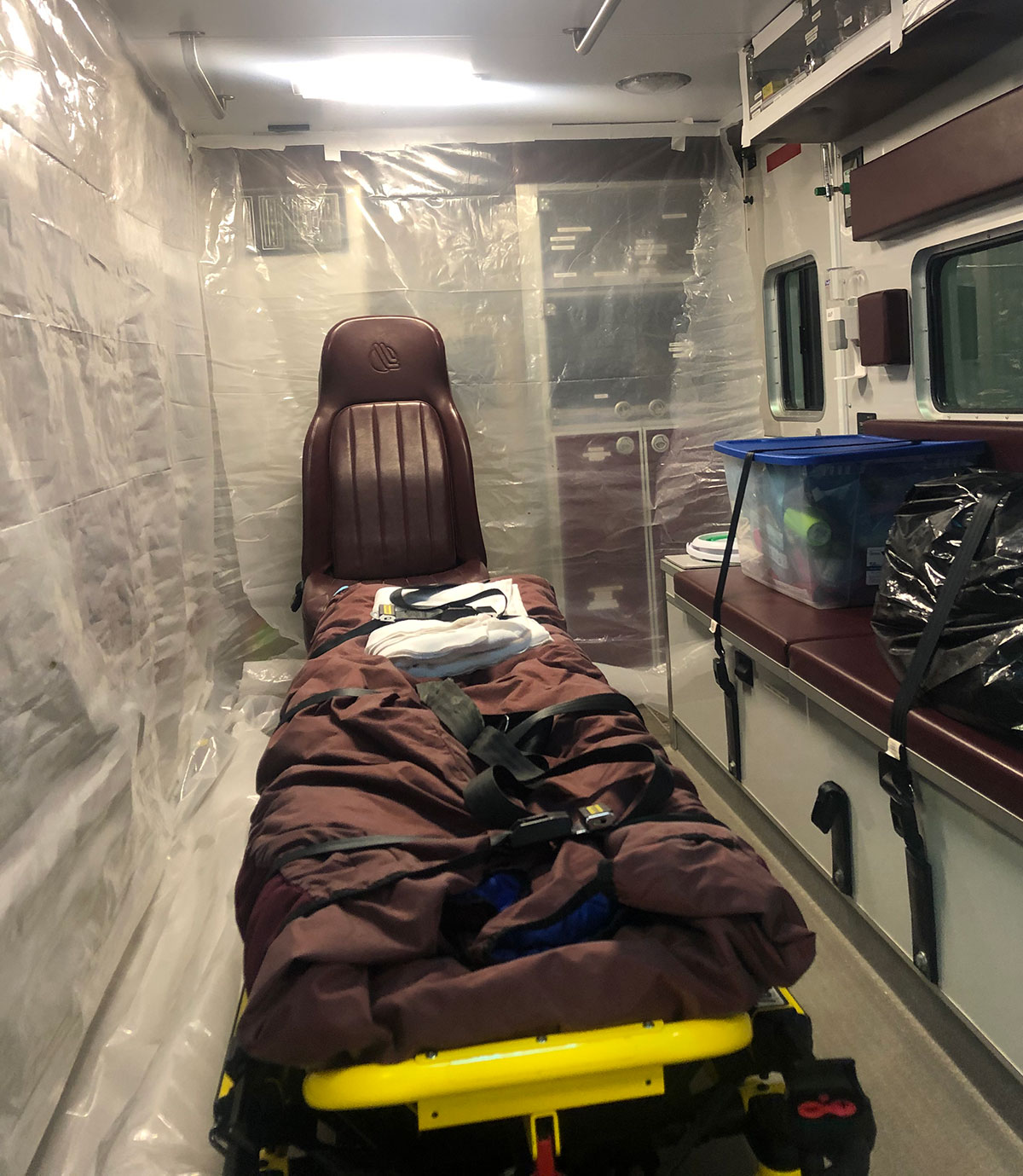 The back of an ambulance with a chair and medical cot, plastic covering the walls, a strapped down tote with supplies, and a strapped down garbage back filled with something.