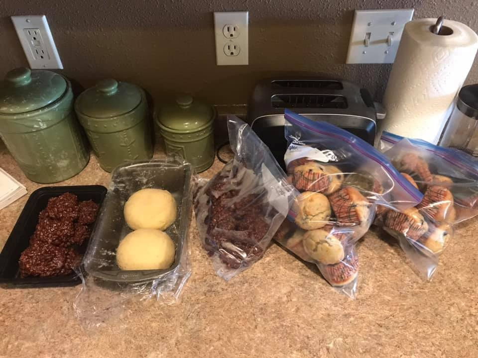 Bags and tins of goodies, including bars, murrins, and and bread, sit on a counter with green jars, paper towels, and a stainless steel toaster behind them.