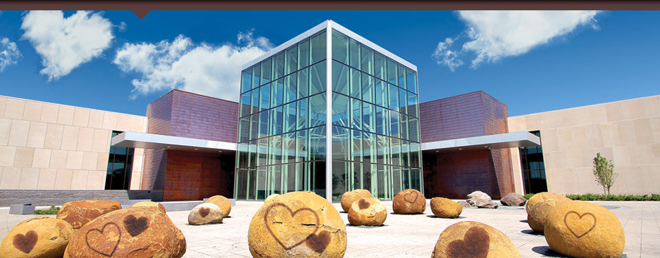 Exterior of building with rocks in front with hearts on them and clouds in the sky with one shaped as a heart