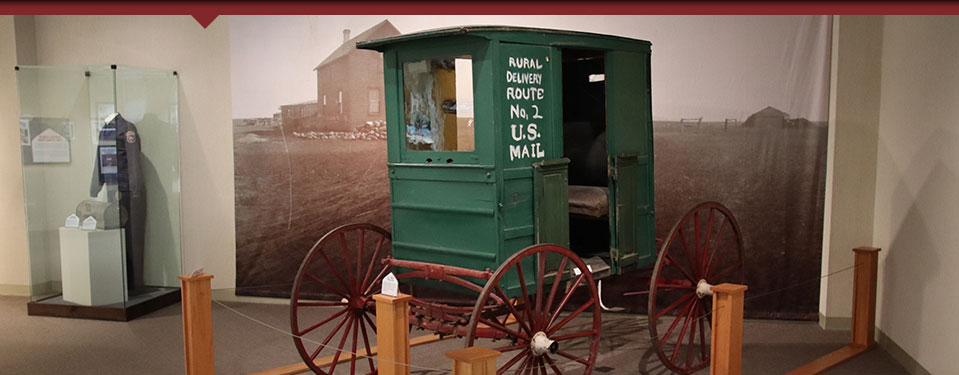 green carriage mail carrier with brown wheels