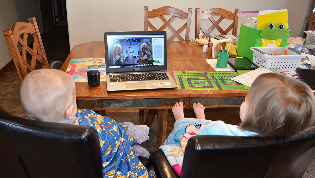 A young boy and girl wrapped in blankets sit in chairs watching a church service from a laptop sitting on a table. Many other items are on the table.