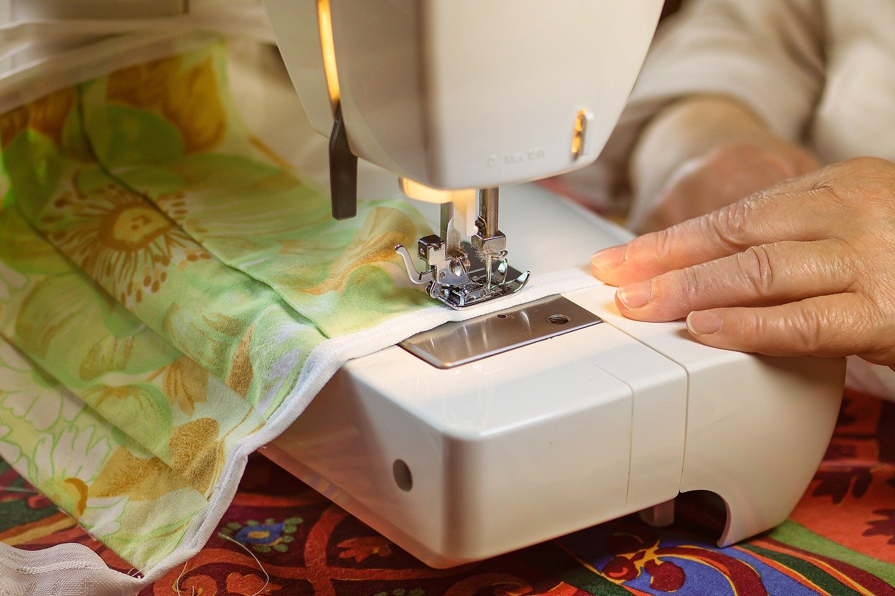 A person's hand is shown using a sewing machine to make a floral patterned mask