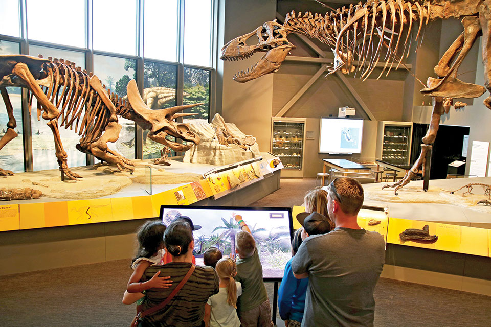 Family standing at dinosaur interactive in the Adaptation Gallery: Geologic Time