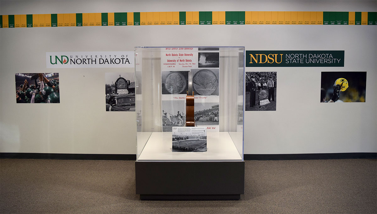 Posters of UND and NDSU football and a timeline showing games played as well as a display case with the Nickel Trophy