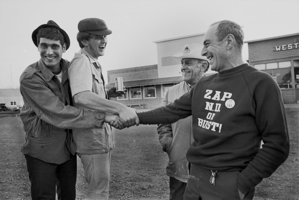Smiling man wearing Zap ND or Bust shirt shakes hands with two smiling young men. Another man stands to the side.