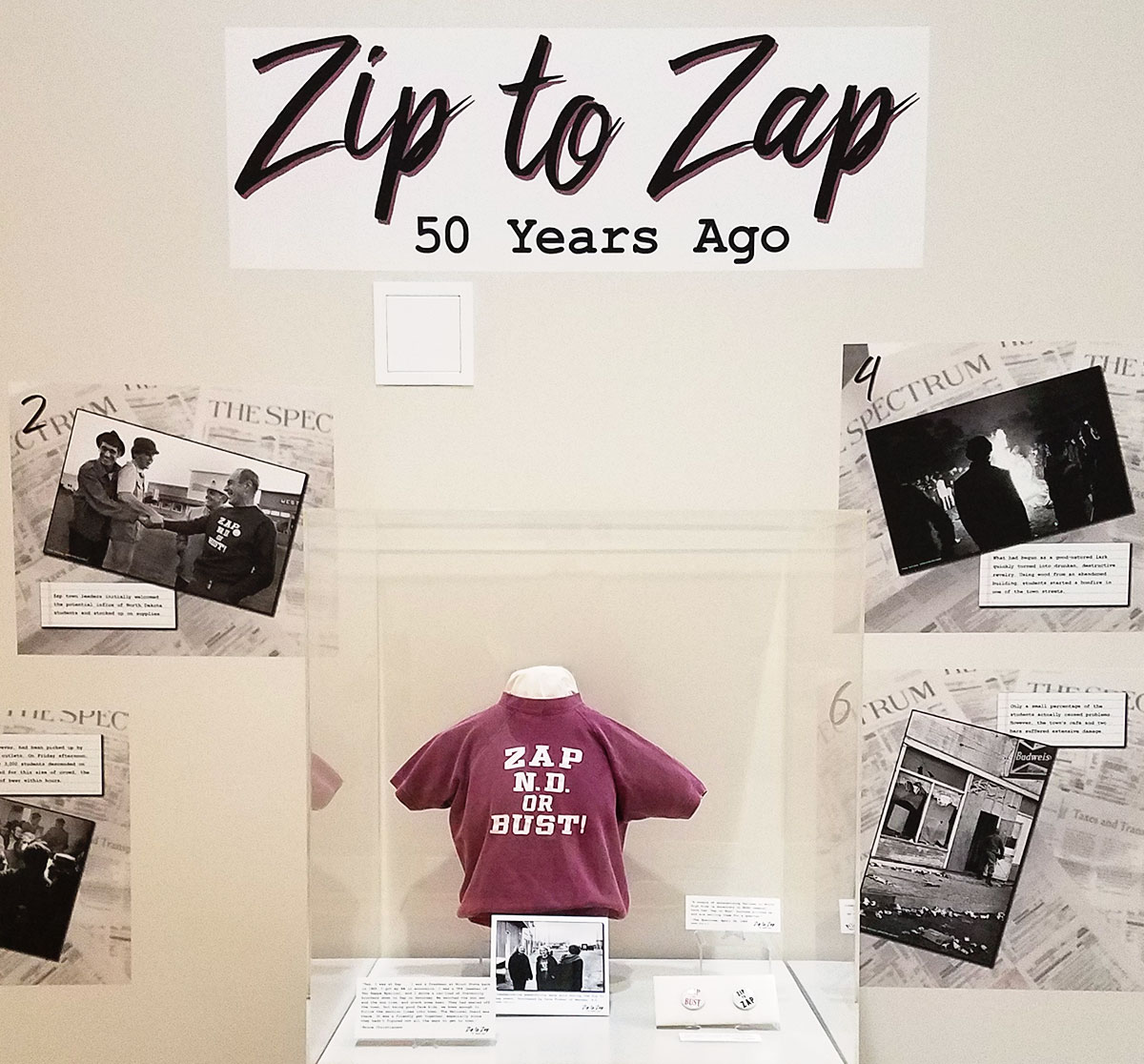 Zip to Zap images and exhibit case containing sweatshirt and pins